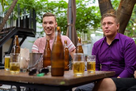 Men talking and laughing while drinking beer outdoors Reklamní fotografie