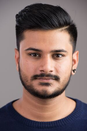 Twarz młodego przystojnego indyjskiego mężczyzny patrzącego na kamerę
