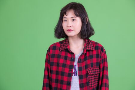 Portrait of beautiful Asian hipster woman thinking