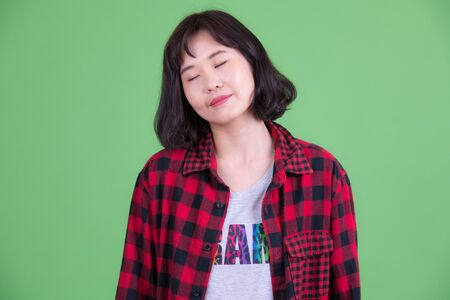 Face of beautiful Asian hipster woman relaxing with eyes closed