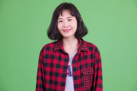 Portrait of happy beautiful Asian hipster woman smiling Stock Photo