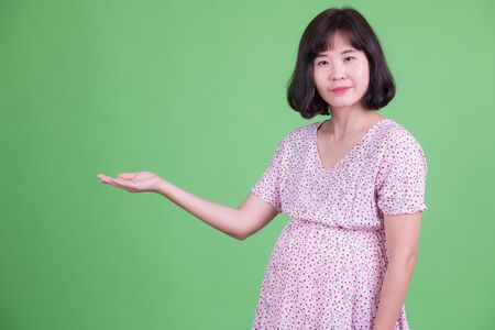 Portrait of beautiful Asian pregnant woman showing something
