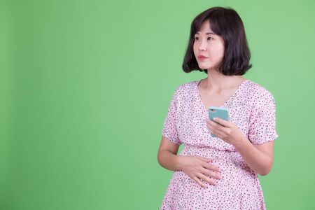 Portrait of Asian pregnant woman thinking while using phone