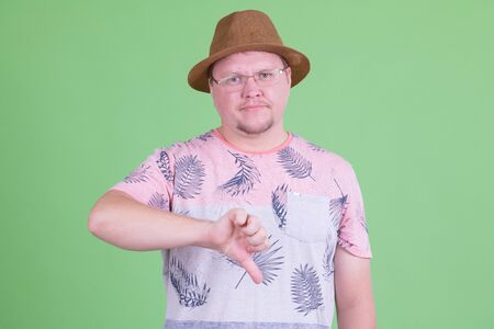 Portrait of stressed overweight bearded tourist man giving thumbs down