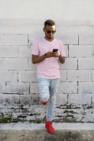 Full body shot of young African man with sunglasses using phone outdoors