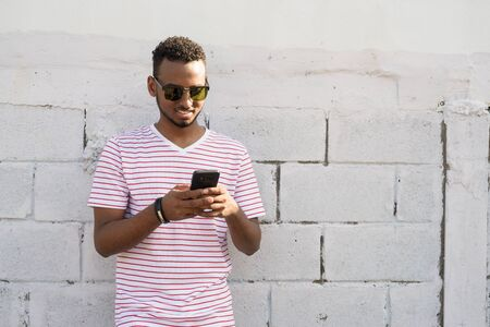Happy young African bearded man with Afro hair using phone outdoors Stock Photo