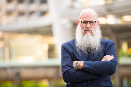Portrait of mature bald businessman with long beard wearing eyeglasses in the city streets outdoors Archivio Fotografico