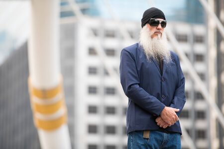 Mature bearded businessman wearing sunglasses and beanie in the city outdoors