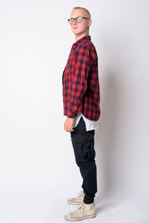 Full body shot profile view of young blonde hipster man looking at camera