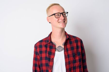 Face of happy young blonde hipster man thinking and looking up
