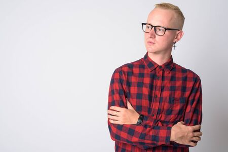 Portrait of young blonde hipster man thinking with arms crossed Stock Photo
