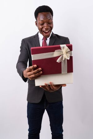 Young handsome African businessman holding gift box against whit