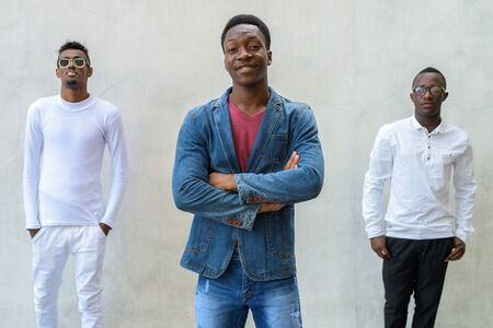 Three young African men hanging out against concrete wall outdoors Фото со стока