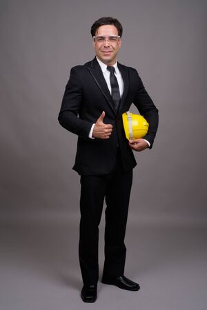 Full body shot of handsome Persian businessman as engineer giving thumbs up 版權商用圖片
