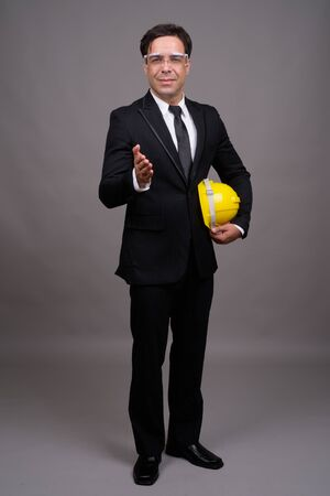 Full body shot of handsome Persian businessman as engineer giving handshake