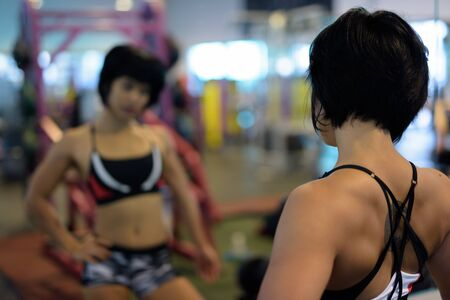 Young beautiful Asian woman looking at mirror in gym