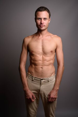 Portrait of handsome man shirtless against gray background