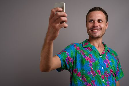 Portrait of handsome tourist man using phone ready for vacation against gray background Stockfoto