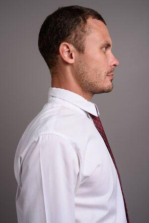 Portrait of handsome businessman against gray background Stockfoto