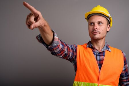 Portrait of handsome man construction worker against gray background Imagens