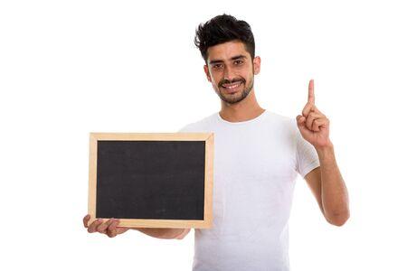 Portrait of young bearded Persian man holding blackboard