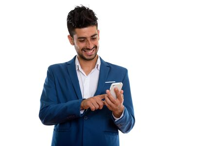 Young handsome bearded Persian businessman in suit using phone