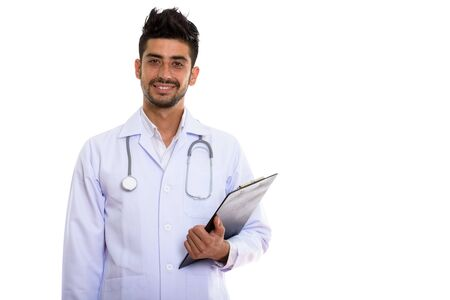 Portrait of young handsome bearded Persian man doctor holding clipboard Stockfoto