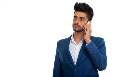 Young handsome bearded Persian businessman talking on the phone Stockfoto