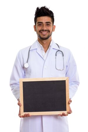 Portrait of young handsome bearded Persian man doctor holding blackboard Stockfoto
