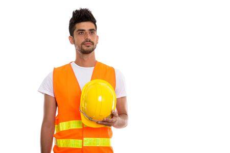 Studio shot of young Persian man construction worker holding saf Zdjęcie Seryjne