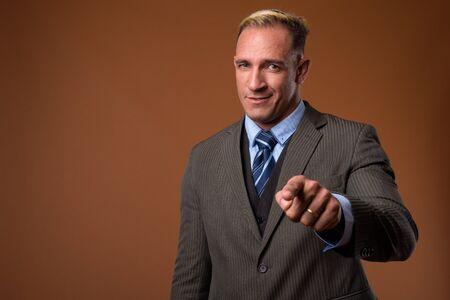 Studio shot of businessman against brown background
