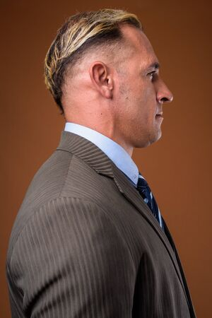 Profile view of businessman against brown background