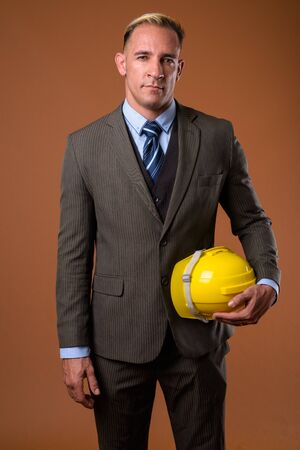 Studio shot of construction businessman holding hardhat