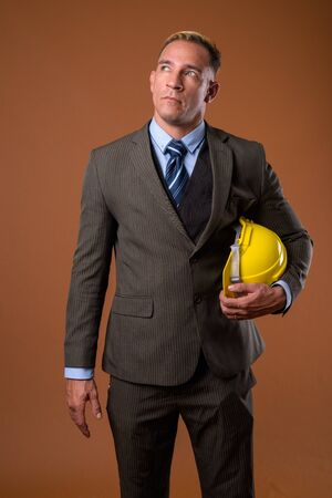 Studio shot of construction businessman thinking and looking up
