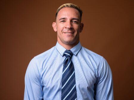 Studio shot of businessman smiling against brown background 写真素材