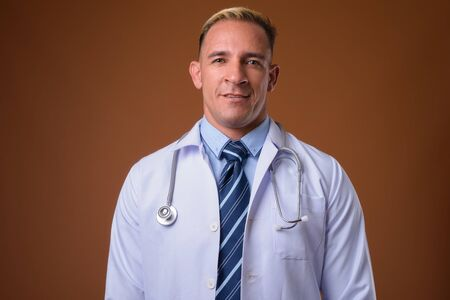 Studio shot of man doctor against brown background 写真素材