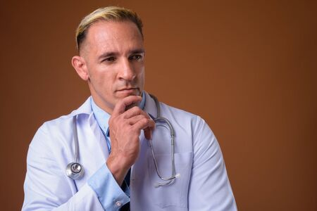 Studio shot of man doctor thinking against brown background Stockfoto