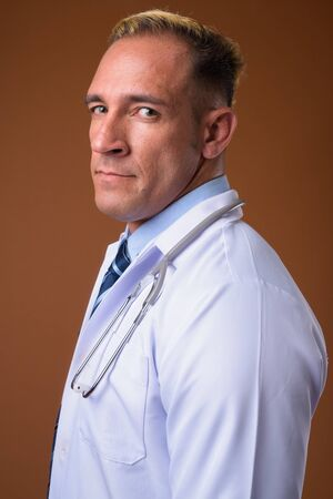 Profile view of man doctor against brown background