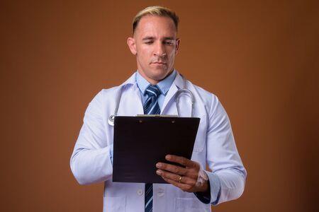 Studio shot of man doctor holding clipboard