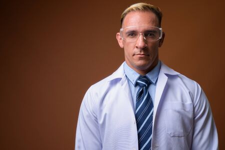 Man doctor wearing protective glasses against brown background 写真素材