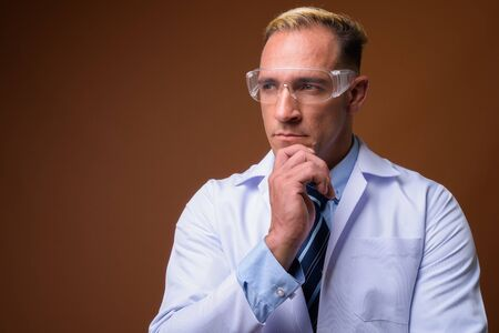 Man doctor wearing protective glasses while thinking Stockfoto