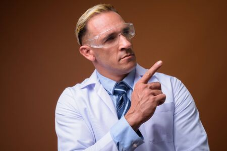 Man doctor wearing protective glasses while thinking 写真素材