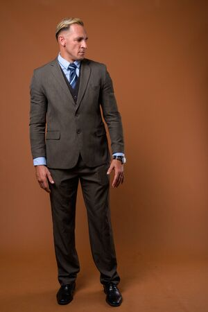 Full body shot of businessman standing against brown background 写真素材