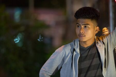Young Asian man thinking in the city streets at night