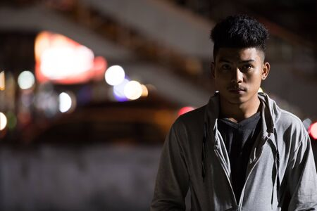 Young Asian man in the city streets at night