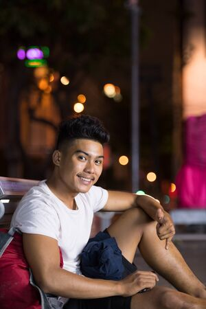 Happy young Asian man sitting in the city streets at night