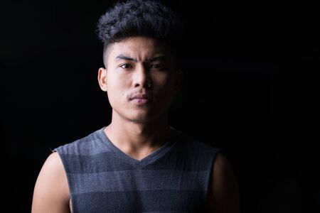 Face of young Asian man at night outdoors
