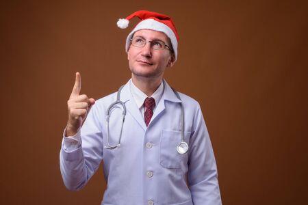 Studio shot of man doctor against brown background Zdjęcie Seryjne