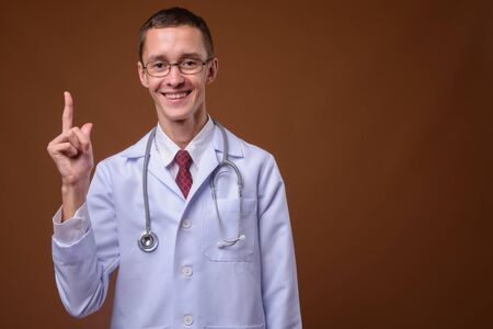 Studio shot of young man doctor against brown background