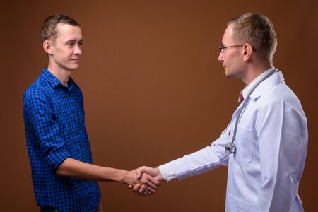 Man doctor and young man patient against brown background